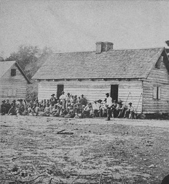 1862 photograph of the slave quarter at Smiths Plantation in Port Royal, South Carolina. The slave house shown is of the saddlebag type.