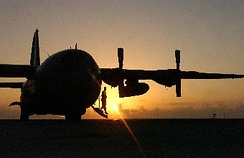 A 321st Expeditionary Maintenance Squadron crew chief, emerges from a C-130 Hercules after conducting a pre-flight inspection.