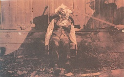 Body of a lynched black male, propped up in a rocking chair for a photograph, circa 1900. Paint has been applied to his face, circular disks glued to his cheeks, cotton glued to his face and head, while a rod props up the victim's head.