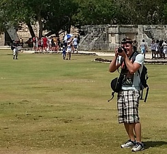 A tourist taking photographs and video at the archaeological site of Chichén Itza.