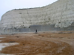 To the east of Brighton, chalk cliffs protected by a sea-wall rise from the beach.