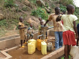 Photograph depicting one adult and five children filling jerrycans at a rural metal water pump with concrete base, at the bottom of a steep rocky hillside