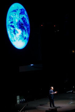 A man is standing on a stage in front of a giant projection of the Earth