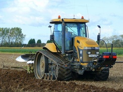 An agricultural tractor with rubber tracks, mitigating soil compaction
