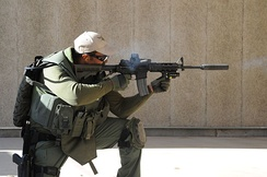 An officer firing during a SWAT training exercise.