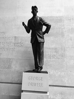 "Statue of George Orwell outside Broadcasting House, headquarters of the BBC. A defence of free speech in an open society, the wall behind the statue is inscribed with the words ""If liberty means anything at all, it means the right to tell people what they do not want to hear"", words from George Orwell's proposed preface to Animal Farm.[47]"