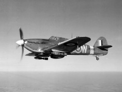 A Hawker Hurricane Mark IIE of No. 402 Squadron RCAF based at Warmwell, England, in flight carrying two 250-lb GP bombs.