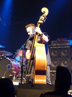 "Psychobilly bassist Jimbo Wallace onstage with Reverend Horton Heat; note his large bass stack consisting of a 15-inch cabinet, a quadruple 10-inch cabinet, and an amplifier ""head""."