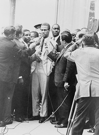 Malcolm X is surrounded by reporters with microphones, while a television camera captures the scene