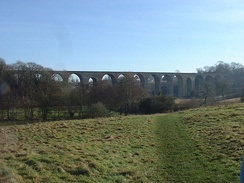 stone viaduct with multiple arches, partly obscured by trees