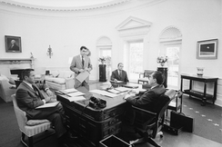 Richard Nixon sitting behind the Wilson desk with three chief advisers surrounding the desk.