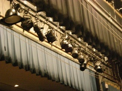 Many stage lights hang on a batten focused in several directions