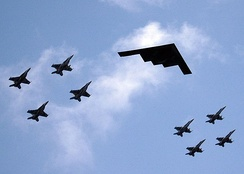 A B-2 in formation flight with eight U.S. Navy F/A-18 Hornets and Super Hornets