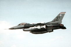 May 1992 air-to-air view of an F-16 Fighting Falcon equipped with an AGM-84 Harpoon all-weather anti-ship missile over Eglin Air Force Base. Note Air Force Systems Command badge on vertical fin.