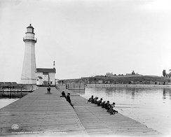 Fishing at Pierhead Light in Oswego, New York, c. 1900.  Fort Ontario behind.