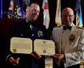Adm. Robert J. Papp Jr. (right), commandant of the U.S. Coast Guard, presents a Coast Guard auxiliarist with the Coast Guard Auxiliary Commendation Medal in 2013.
