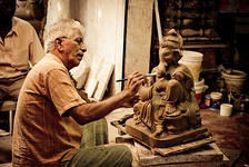 Man painting a statue of Ganesh