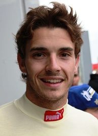 Man in his early twenties with a head full of hair and smiling. He is wearing white racing overalls.