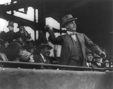 Speaker Longworth throws out the first ball at the starting game at Griffith Stadium, Mrs. Longworth seated below, May 3, 1928.