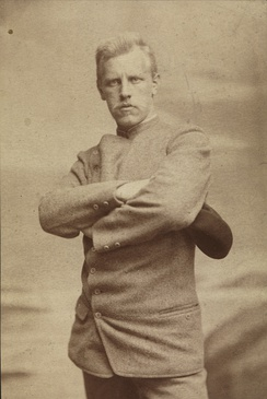 Portrait of a stern and determined looking man with arms crossed.
