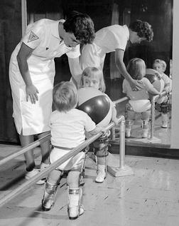 Физический терапевт (специалист по реабилитации) помогает детям, больным полиомиелитом, стоять на ногах, держась за поручни