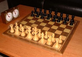 This photo shows a chessboard with pieces set up on both sides, ready to play. A chess clock is at the side.