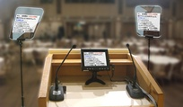 A set of three teleprompters displaying text in the Japanese language