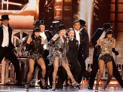 Madonna in a shiny dress, flanked by male dancers in coattails.