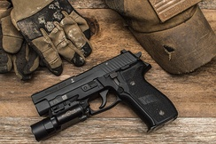 A P226 Mk25 model featuring the UID barcode, Silver Anchor and a Surefire X300 Ultra weapon light mounted on the Picatinny rail.