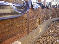 A soldier pile wall using reclaimed railway sleepers as lagging.