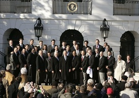 Group of about thirty men wearing suits in front of a white building