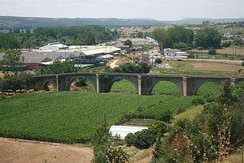 Coria old bridge. The river has changed course, and no longer flows beneath the bridge. Instead there are fields of green crops