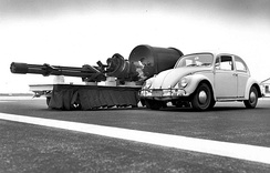 The GAU-8/A Avenger Gatling gun next to a Volkswagen Beetle. Removing an installed GAU-8 from an A-10 requires first installing a jack under the aircraft's tail to prevent it from tipping, as the cannon makes up most of the aircraft's forward weight.