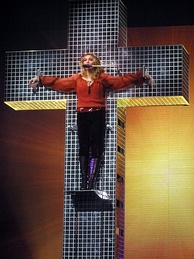 An image showing a blue crystal cross and a blond woman standing on a platform on the cross. The woman is wearing a red shirt and dark brown pants. Her hands are spread apart along the cross's breadth to symbolize as if she has been crucified. Behind the cross, a backdrop is centrally illuminated