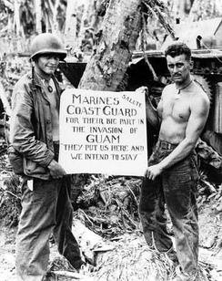Marine Corps Privates First Class William A. McCoy and Ralph L. Plunkett holding a sign thanking the Coast Guard after the Battle of Guam in 1944[41]