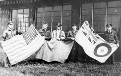British and American personnel hold up flags at the 496th Fighter Training Group base in Goxhill., 1944