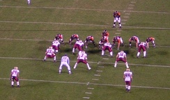 This defense (in white) is in a base 4-3 set. Just behind the four defensive linemen (whose hands are on the ground) are three linebackers (Nos. 55, 3 and 16), and further back are two safeties (numbers 24 and 44).