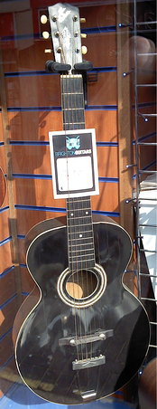 "A 1918 ""The Gibson"" acoustic guitar, with a 13th fret neck join, circular sound hole, and floating bridge. This was a transitional model with no f-holes and a much smaller body than the classic archtop."
