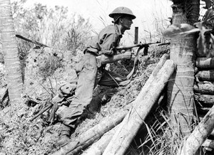 Black and white photo of a man who is wearing a military uniform and armed with a gun crouching on a step incline.