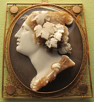 Black and white stone cameo of a woman facing left with flowers and leaves in her hair