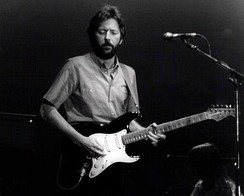 A black and white photograph of Eric Clapton with a guitar on stage