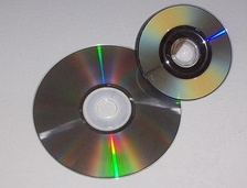 Shown is a CD-ROM (left) and a game in Nintendo's proprietary optical disc format similar to a MiniDVD, as the most widely used forms of optical media are DVDs and compact discs