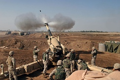 Marines from Mike Battery, 4th Battalion, 14th Marines an activated reserve artillery unit, operate the 155 mm M198 howitzer in November 2004 supporting Operation Phantom Fury.