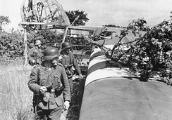 An abandoned Waco CG-4 glider is examined by German troops