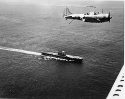 An SBD flies over Enterprise. The carrier Saratoga is in the distant background near the top of the photo.