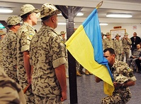Henadii Lachkov, commander of the Ukrainian contingent in Iraq, kisses his country's flag