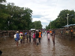 People stand in a flooded street that usually serves as a farmers market, in Ouanaminthe, northeast Haiti, September 8, 2017.