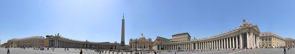 Panorama showing the façade of St. Peter's at the centre with the arms of Bernini's colonnade sweeping out on either side. It is midday and tourists are walking and taking photographs.