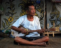 A music teacher in Mae On, near Chiang Mai, playing a sueng.