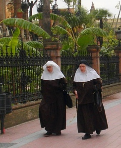 A novice is at left. The habit of a novice often differs from that of the full professed nuns or monks.
